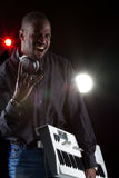 Young black music producer. Young black man with a keyboard and headphones over black background Stock Photo
