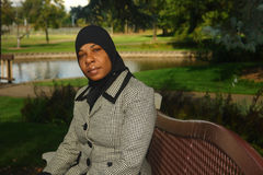 Young Black Muslim Woman. A picture of a young black Muslim woman sitting on a bench Stock Image