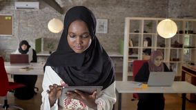 Young black muslim women in hijab using tablet, looking in camera, smiling, islamic business womens typing on laptop in. Modern office stock footage