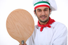 Young black pizza chef. Young black pizza cook taking a spade Stock Images