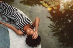 Young black pregnant woman is laying near a tropical pond royalty free stock images