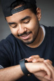 Young black rapper guy using smart wrist watch royalty free stock photography