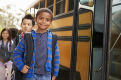 Young black schoolboy and friends wait to get on school bus stock images
