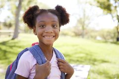 Young black schoolgirl smiling to camera, portrait royalty free stock photos