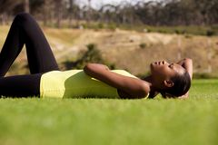 Young black sports woman lying down on grass Royalty Free Stock Images