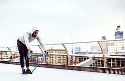 Young black sportsman exercising with elastic rubber bands in London. Young active black sportsman exercising with elastic rubber bands on the bridge in London royalty free stock photos