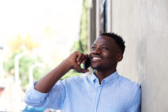 Young black standing outside by wall and talking on mobile phone Royalty Free Stock Image