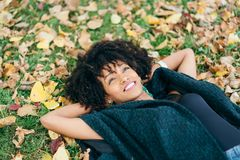 Afro hair style woman daydraming in autumn. Young black successful woman with afro hair style relaxing in autumn. Happiness and relax concept stock photo