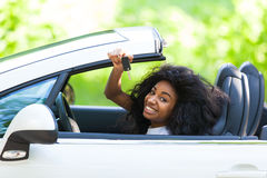 Young black teenage driver holding car keys driving her new car Royalty Free Stock Photos