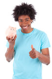 Young black teenage men holding a piggy bank and minking thumbs Royalty Free Stock Photography