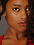Young Black Woman. Lovely Closeup of beautiful Black woman on grey Royalty Free Stock Images