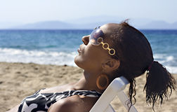 Young black woman. Sunbathing with sunglasses on Royalty Free Stock Photography