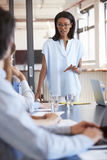 Young black woman addressing team at meeting, vertical Stock Photography