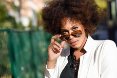 Young black woman with afro hairstyle with aviator sunglasses. Young black woman with afro hairstyle standing in urban background with aviator sunglasses. Mixed Royalty Free Stock Photos