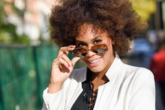 Young black woman with afro hairstyle with aviator sunglasses. Young black woman with afro hairstyle standing in urban background with aviator sunglasses. Mixed Stock Image