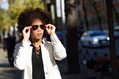 Young black woman with afro hairstyle with aviator sunglasses. Young black woman with afro hairstyle standing in urban background with aviator sunglasses. Mixed Royalty Free Stock Image