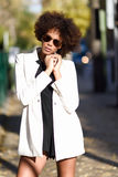 Young black woman with afro hairstyle with aviator sunglasses. Young black woman with afro hairstyle standing in urban background with aviator sunglasses. Mixed Stock Photo