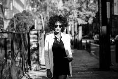 Young black woman with afro hairstyle with aviator sunglasses. Young black woman with afro hairstyle standing in urban background with aviator sunglasses. Mixed Royalty Free Stock Photo