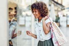 Free Young Black Woman, Afro Hairstyle, Looking At A Shop Window Royalty Free Stock Photos - 109589448