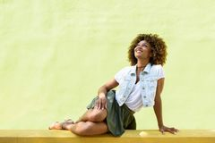 Young black woman, afro hairstyle, sitting on an urban wall Royalty Free Stock Images