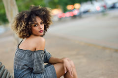Young black woman with afro hairstyle smiling in urban backgroun Royalty Free Stock Image