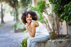 Young black woman with afro hairstyle smiling in urban park Royalty Free Stock Photography