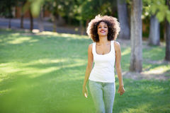 Young black woman with afro hairstyle smiling in urban park Stock Photo
