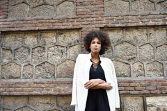 Young black woman with afro hairstyle standing in urban backgrou. Nd. Mixed girl wearing white blazer jacket and black dress posing near a brick wall. Fashion Stock Image