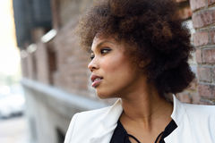 Young black woman with afro hairstyle standing in urban backgrou Stock Photo