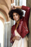 Young black woman with afro hairstyle standing in urban backgrou. Young black female with afro hairstyle standing in an urban street. Mixed woman wearing red Royalty Free Stock Photos