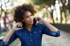 Young black woman with afro hairstyle standing in urban backgrou. Young black woman with afro hairstyle listening to the music with headphones in urban Royalty Free Stock Image