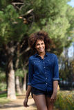 Young black woman with afro hairstyle walking in urban park. Mixed woman wearing blue shirt and shorts. Female smiling Stock Photo