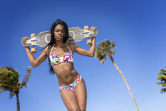 Young black woman in bikini, holding a skateboard behind her head. Royalty Free Stock Photos