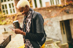 Young black woman with coffee cup and mobile phone on the street Royalty Free Stock Photos