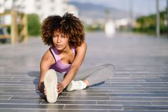 Young black woman doing stretching after running outdoors. Girl exercising with city scape at the background. Afro hair Royalty Free Stock Image