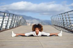 Young black woman doing stretching after running outdoors. Girl exercising with city scape at the background. Afro hair Royalty Free Stock Images