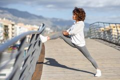 Young black woman doing stretching after running outdoors. Girl exercising with city scape at the background. Afro hair Royalty Free Stock Photos