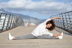 Young black woman doing stretching after running outdoors. Girl exercising with city scape at the background. Afro hair Royalty Free Stock Photography