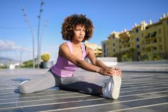 Young black woman doing stretching after running outdoors. Girl exercising with city scape at the background. Afro hair Stock Photos