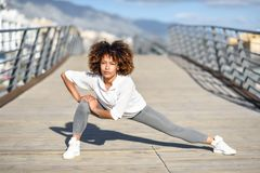 Young black woman doing stretching after running outdoors. Girl exercising with city scape at the background. Afro hair Stock Images