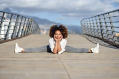 Young black woman doing stretching after running outdoors. Girl exercising with city scape at the background. Afro hair Royalty Free Stock Photo