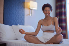 Young black woman doing yoga at home in the lotus position. Young black woman doing yoga in bed Stock Image