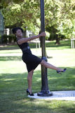Young black woman in dress holdig on to pole Royalty Free Stock Image
