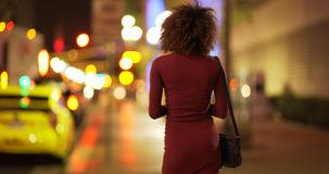 Young black woman in dress waiting for date on sidewalk in Los Angeles Stock Photo
