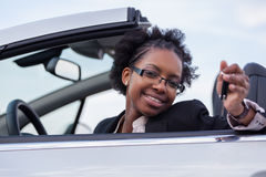 Young black woman driver holding car keys. Young beautiful black woman driver holding car keys driving her new car Royalty Free Stock Photo