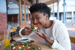 Young black woman eating vegetarian pizza Royalty Free Stock Photo