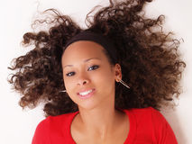 Young black woman on floor smiling. Young black woman on back with hair spread out Royalty Free Stock Images