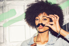 Young black woman having fun with a fake mustache. Young black women having fun with a fake mustache stock photo