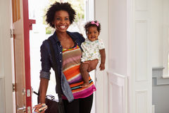 Young black woman holding child arriving home. Young black women holding child arriving home stock photography