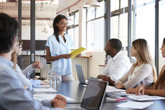 Young black woman holding document addresses team at meeting. Young black women holding document addresses team at meeting Stock Photography